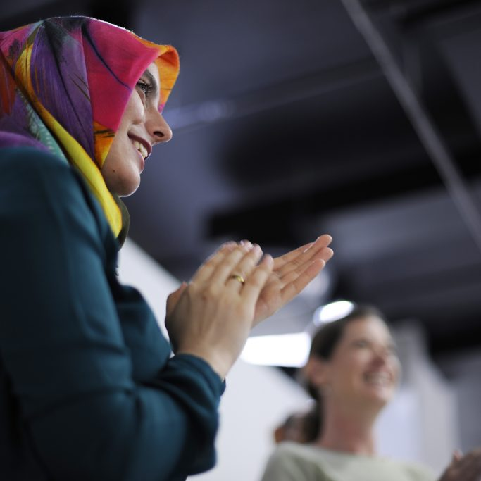 Woman with headscarf clapping